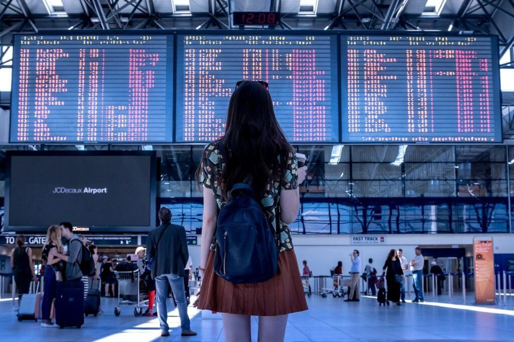 空港のフライト日程板を見ている女性の後ろ姿