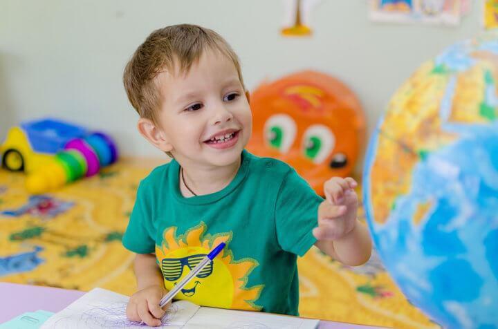 地球儀で遊ぶ男の子の画像