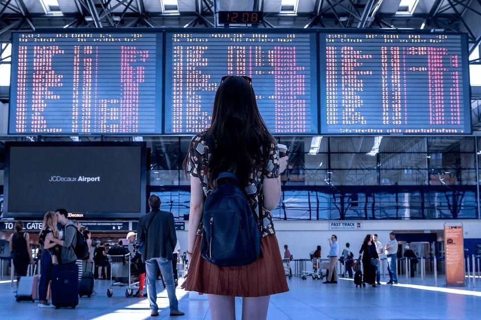 空港で掲示板を見ながら佇む女性