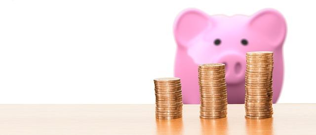 豚と積み立てた硬貨の画像