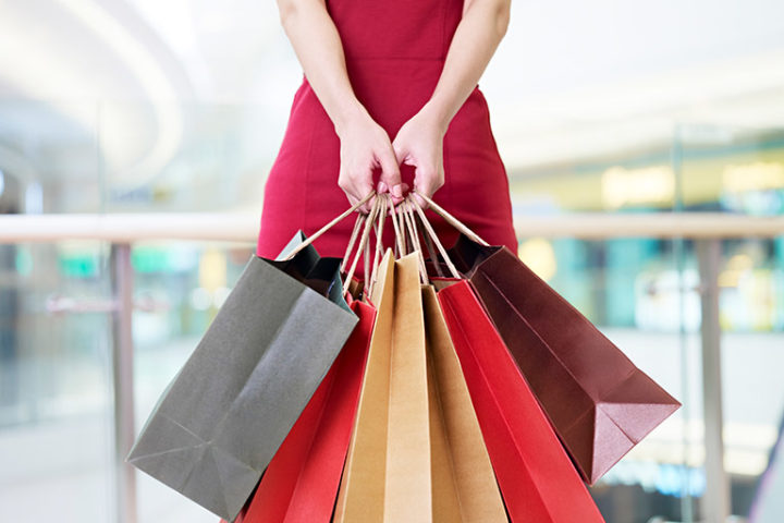 買い物袋を大量にぶら下げる女性の画像